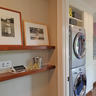 Small transitional single-wall utility room in Chicago with white cabinets, purple walls, medium hardwood floors, a stacked washer and dryer, raised-panel cabinets and quartz benchtops.