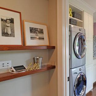 Cette image montre une petite buanderie linéaire traditionnelle multi-usage avec des portes de placard blanches, un mur violet, un sol en bois brun, des machines superposées, un placard avec porte à panneau surélevé et un plan de travail en quartz modifié.