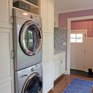 Inspiration for a small transitional single-wall medium tone wood floor utility room remodel in Chicago with white cabinets, purple walls, a stacked washer/dryer, raised-panel cabinets, quartz countertops and an undermount sink