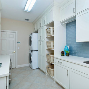 Example of a mid-sized transitional galley porcelain tile utility room design in Miami with recessed-panel cabinets, white cabinets, solid surface countertops, a stacked washer/dryer, an undermount sink and beige walls