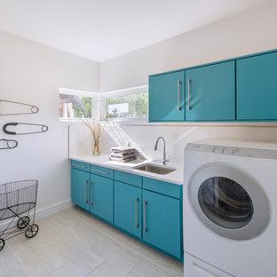Immagine di una sala lavanderia design con lavello sottopiano, ante lisce, ante blu, pareti bianche e lavatrice e asciugatrice affiancate