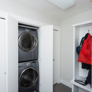 This is an example of a small modern single-wall laundry cupboard in Calgary with beige walls, porcelain flooring, a stacked washer and dryer and green floors.