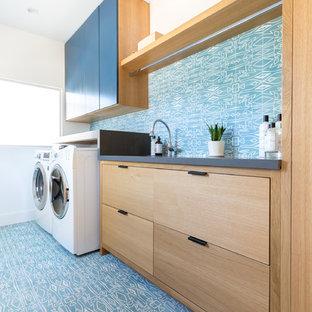 Exempel på en stor modern grå linjär grått tvättstuga enbart för tvätt, med en undermonterad diskho, släta luckor, bänkskiva i kvarts, blå väggar, en tvättmaskin och torktumlare bredvid varandra, skåp i mellenmörkt trä och blått golv