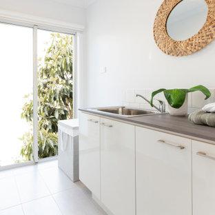 Immagine di una sala lavanderia tropicale di medie dimensioni con ante bianche, top in quarzo composito, paraspruzzi bianco, paraspruzzi con piastrelle in ceramica, pareti bianche, pavimento con piastrelle in ceramica, pavimento grigio e top grigio