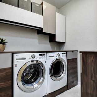 Esempio di una sala lavanderia design di medie dimensioni con ante lisce, ante in legno bruno, top in legno, pareti grigie, pavimento in cemento, lavatrice e asciugatrice affiancate, pavimento grigio e top marrone