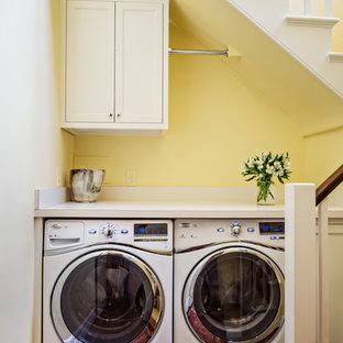 Ispirazione per una piccola lavanderia multiuso tradizionale con ante con riquadro incassato, ante bianche, top in laminato, pareti gialle, pavimento in legno massello medio e lavatrice e asciugatrice affiancate