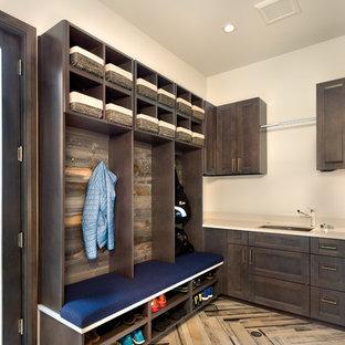 Foto di una lavanderia multiuso boho chic di medie dimensioni con lavello sottopiano, ante con riquadro incassato, ante grigie, top in quarzo composito, pareti bianche, pavimento con piastrelle in ceramica e pavimento beige