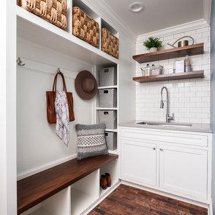 Immagine di una piccola lavanderia multiuso country con lavello sottopiano, ante in stile shaker, ante bianche, pareti bianche, pavimento marrone, top in superficie solida, pavimento in legno massello medio e top grigio