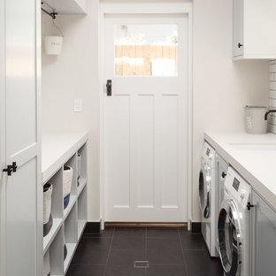Foto di una piccola sala lavanderia stile marino con ante bianche, pareti bianche, lavatrice e asciugatrice affiancate, pavimento nero e ante in stile shaker