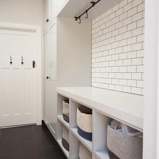 Idéer för små maritima parallella tvättstugor enbart för tvätt, med släta luckor, vita skåp, vita väggar, en tvättmaskin och torktumlare bredvid varandra och svart golv
