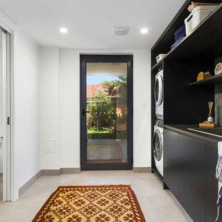 Idée de décoration pour une buanderie parallèle design dédiée avec un évier posé, un placard à porte plane, des portes de placard noires, un mur blanc, des machines superposées, un sol gris et un plan de travail noir.