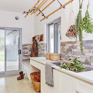 Foto di una grande sala lavanderia tradizionale con lavello a vasca singola, ante in stile shaker, ante bianche, top in laminato, pareti bianche, pavimento in cemento, pavimento grigio e top grigio