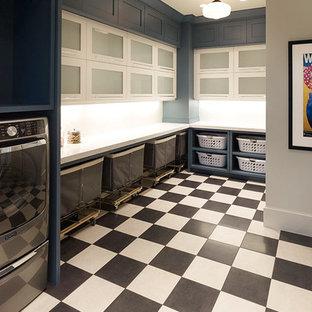 Foto på en mycket stor lantlig vita l-formad tvättstuga enbart för tvätt, med luckor med glaspanel, vita skåp, bänkskiva i kvarts, grå väggar, klinkergolv i porslin, en tvättmaskin och torktumlare bredvid varandra och flerfärgat golv