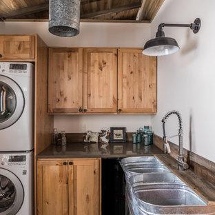 Idee per una sala lavanderia rustica di medie dimensioni con lavatoio, ante in stile shaker, pareti bianche, lavatrice e asciugatrice a colonna, pavimento grigio, top grigio, pavimento in cemento, ante in legno scuro e top in superficie solida