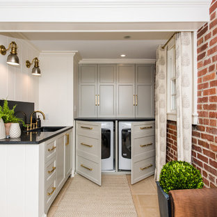 Inspiration for a small transitional l-shaped ceramic floor and beige floor laundry room remodel in DC Metro with an undermount sink, recessed-panel cabinets, gray cabinets, granite countertops, white walls and a concealed washer/dryer