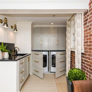 Неиссякаемый источник вдохновения для домашнего уюта: маленькая угловая прачечная в стиле современная классика с врезной раковиной, фасадами с утопленной филенкой, серыми фасадами, гранитной столешницей, белыми стенами, полом из керамической плитки, со скрытой стиральной машиной и бежевым полом