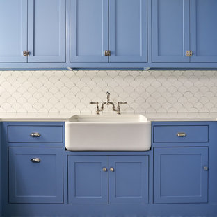 Inspiration for a transitional blue floor laundry room remodel in Dallas with a farmhouse sink, shaker cabinets, blue cabinets, white walls and white countertops