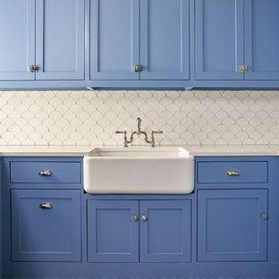 Immagine di una sala lavanderia classica di medie dimensioni con lavello stile country, ante in stile shaker, ante blu, pareti bianche, pavimento blu, top bianco, top in superficie solida e pavimento con piastrelle in ceramica