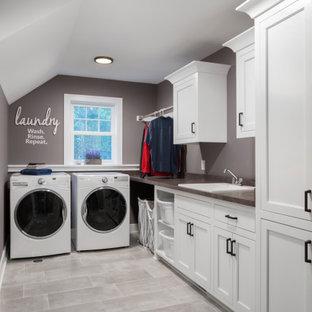 Immagine di una sala lavanderia classica di medie dimensioni con lavello da incasso, ante in stile shaker, ante bianche, pareti grigie, lavatrice e asciugatrice affiancate, pavimento grigio, top marrone, top in laminato e pavimento con piastrelle in ceramica