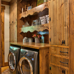 Mid-sized mountain style single-wall brick floor and multicolored floor laundry room photo in Minneapolis with medium tone wood cabinets, wood countertops, white walls, a side-by-side washer/dryer, brown countertops and flat-panel cabinets