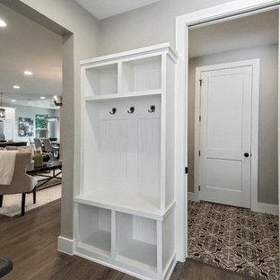 Idee per una piccola lavanderia classica con ante con riquadro incassato, ante bianche, pareti beige, pavimento in gres porcellanato, lavatrice e asciugatrice affiancate, pavimento marrone e top beige
