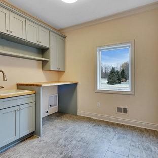 Inspiration för stora klassiska linjära brunt tvättstugor enbart för tvätt, med en nedsänkt diskho, skåp i shakerstil, grå skåp, träbänkskiva, beige väggar, laminatgolv, en tvättmaskin och torktumlare bredvid varandra och grått golv