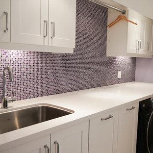 Foto på en mellanstor funkis parallell tvättstuga, med en undermonterad diskho, skåp i shakerstil, vita skåp, bänkskiva i kvarts, lila väggar och en tvättmaskin och torktumlare bredvid varandra