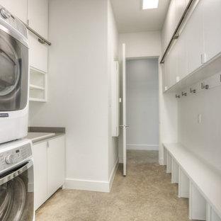 Modern inredning av ett mellanstort parallellt grovkök, med en nedsänkt diskho, släta luckor, vita skåp, vita väggar, betonggolv, en tvättpelare, beiget golv och laminatbänkskiva