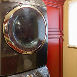 Foto di una lavanderia multiuso minimal con lavello a vasca singola, ante con bugna sagomata, ante rosse, top in granito, pareti beige, pavimento in pietra calcarea e lavatrice e asciugatrice a colonna