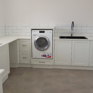 Photo of a large contemporary u-shaped separated utility room in Other with an utility sink, shaker cabinets, white cabinets, engineered stone countertops, white walls, ceramic flooring, a stacked washer and dryer, grey floors and yellow worktops.