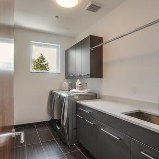 Inredning av en modern mellanstor parallell tvättstuga enbart för tvätt, med en undermonterad diskho, släta luckor, grå skåp, bänkskiva i koppar, vita väggar, klinkergolv i keramik, en tvättmaskin och torktumlare bredvid varandra och grått golv