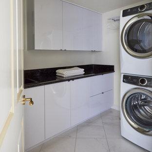 Idéer för små funkis linjära svart tvättstugor enbart för tvätt, med en undermonterad diskho, släta luckor, vita skåp, granitbänkskiva, svart stänkskydd, vita väggar, marmorgolv, en tvättpelare och vitt golv