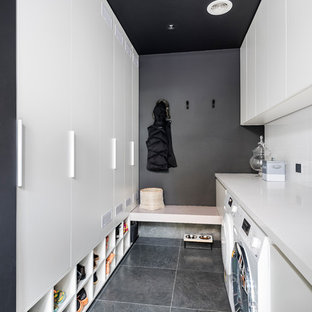 Photo of a large modern galley utility room in Melbourne with flat-panel cabinets, white cabinets, engineered stone countertops, porcelain flooring, a side by side washer and dryer, grey floors, white worktops and grey walls.