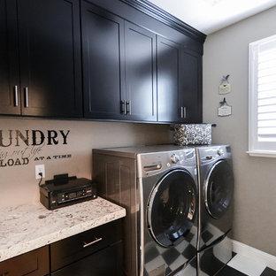 Immagine di una sala lavanderia classica di medie dimensioni con ante in stile shaker, ante nere, top in granito, pareti grigie, pavimento in linoleum e lavatrice e asciugatrice affiancate
