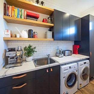 Foto på en mellanstor funkis vita linjär tvättstuga enbart för tvätt, med en enkel diskho, släta luckor, svarta skåp, bänkskiva i kvarts, vita väggar, ljust trägolv och gult golv