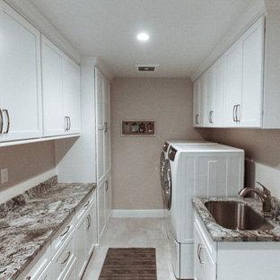 Idéer för en mellanstor klassisk parallell tvättstuga enbart för tvätt, med en undermonterad diskho, vita skåp, granitbänkskiva, beige stänkskydd, stänkskydd i marmor, luckor med infälld panel, beige väggar, klinkergolv i porslin, en tvättmaskin och torktumlare bredvid varandra och beiget golv