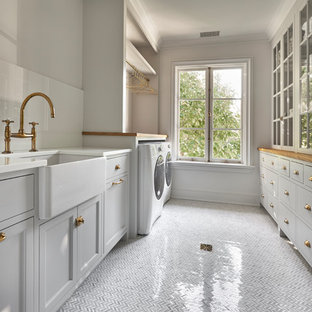 Laundry room - transitional marble floor laundry room idea in New York with glass countertops