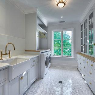 Immagine di una lavanderia classica con top in vetro e pavimento in marmo