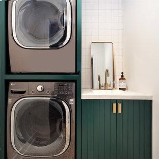 Foto de cuarto de lavado lineal, escandinavo, pequeño, con puertas de armario verdes, encimera de cuarcita, paredes blancas, lavadora y secadora apiladas, encimeras blancas y fregadero de un seno