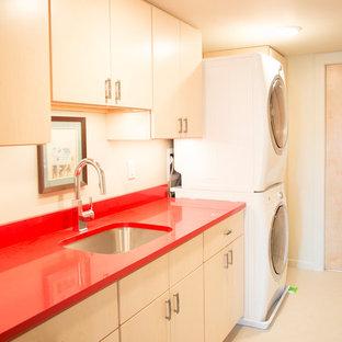 Exemple d'une buanderie linéaire tendance dédiée avec un évier utilitaire, un placard à porte plane, des machines superposées et un plan de travail rouge.