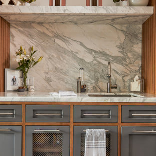 Large mid-century modern galley concrete floor and gray floor utility room photo in Los Angeles with a drop-in sink, shaker cabinets, gray cabinets, quartz countertops, quartz backsplash, white walls and a stacked washer/dryer