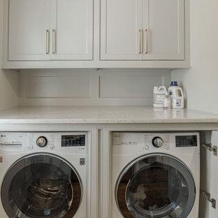 Foto på ett litet vintage vit parallellt grovkök, med luckor med profilerade fronter, grå skåp, marmorbänkskiva, stänkskydd med metallisk yta, spegel som stänkskydd, vita väggar, mörkt trägolv, en tvättmaskin och torktumlare bredvid varandra och brunt golv