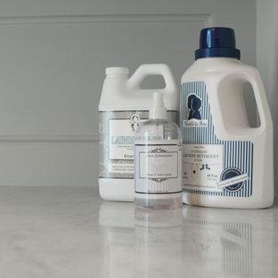 Klassisk inredning av ett litet vit parallellt vitt grovkök, med luckor med profilerade fronter, grå skåp, marmorbänkskiva, stänkskydd med metallisk yta, spegel som stänkskydd, vita väggar, mörkt trägolv, en tvättmaskin och torktumlare bredvid varandra och brunt golv