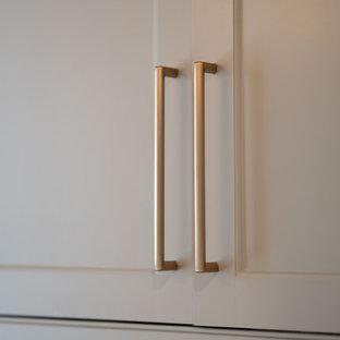 Пример оригинального дизайна: маленькая параллельная универсальная комната в стиле неоклассика (современная классика) с фасадами с декоративным кантом, серыми фасадами, мраморной столешницей, фартуком цвета металлик, зеркальным фартуком, белыми стенами, темным паркетным полом, со стиральной и сушильной машиной рядом, коричневым полом и белой столешницей