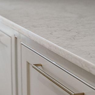 Inspiration för små klassiska parallella vitt grovkök, med luckor med profilerade fronter, grå skåp, marmorbänkskiva, stänkskydd med metallisk yta, spegel som stänkskydd, vita väggar, mörkt trägolv, en tvättmaskin och torktumlare bredvid varandra och brunt golv