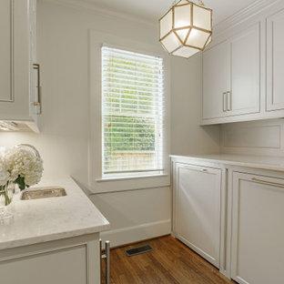 Bild på ett litet vintage vit parallellt vitt grovkök, med luckor med profilerade fronter, grå skåp, marmorbänkskiva, stänkskydd med metallisk yta, spegel som stänkskydd, vita väggar, mörkt trägolv, en tvättmaskin och torktumlare bredvid varandra och brunt golv
