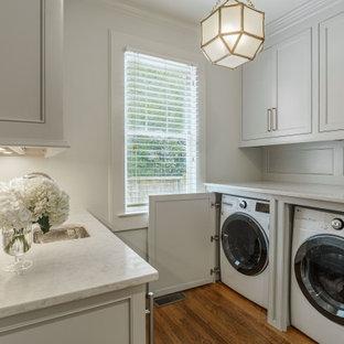 Inredning av ett klassiskt litet vit parallellt vitt grovkök, med luckor med profilerade fronter, grå skåp, marmorbänkskiva, stänkskydd med metallisk yta, spegel som stänkskydd, vita väggar, mörkt trägolv, en tvättmaskin och torktumlare bredvid varandra och brunt golv
