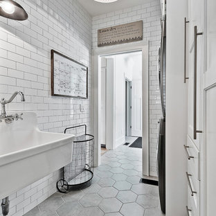 Inspiration for a mid-sized farmhouse single-wall ceramic floor and gray floor dedicated laundry room remodel in Other with an utility sink, white cabinets, a stacked washer/dryer and recessed-panel cabinets