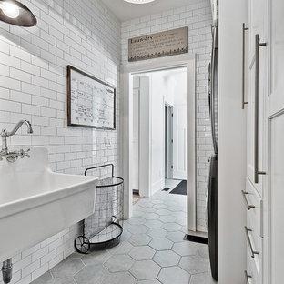Foto di una sala lavanderia country di medie dimensioni con lavatoio, ante bianche, pavimento con piastrelle in ceramica, lavatrice e asciugatrice a colonna, ante con riquadro incassato e pavimento grigio