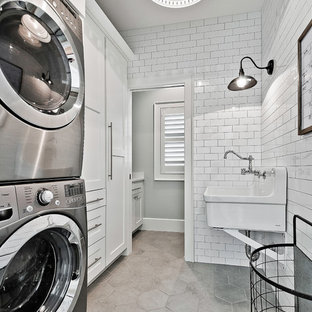 Dedicated laundry room - mid-sized craftsman single-wall ceramic floor dedicated laundry room idea in Other with an utility sink, white cabinets, white walls, a stacked washer/dryer and shaker cabinets